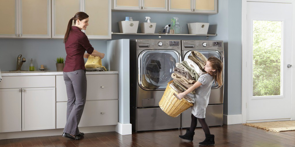 child carrying laundry basket with mom