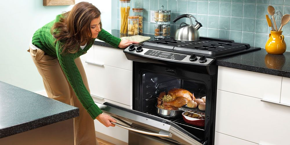woman opening oven with turkey inside.