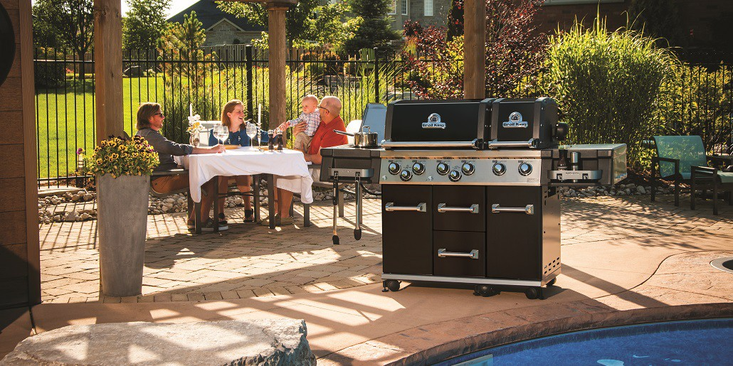 family eating outside with grill and pool