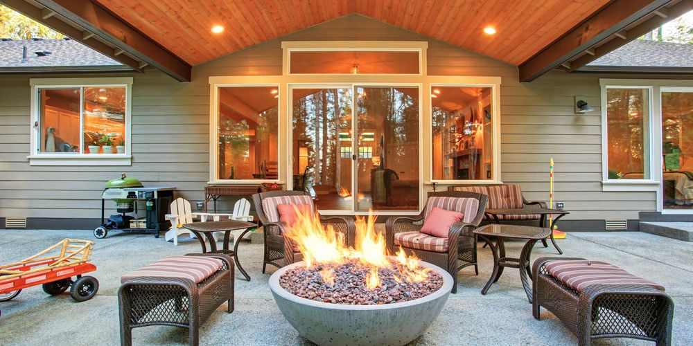 fire pit outside of house with chairs.