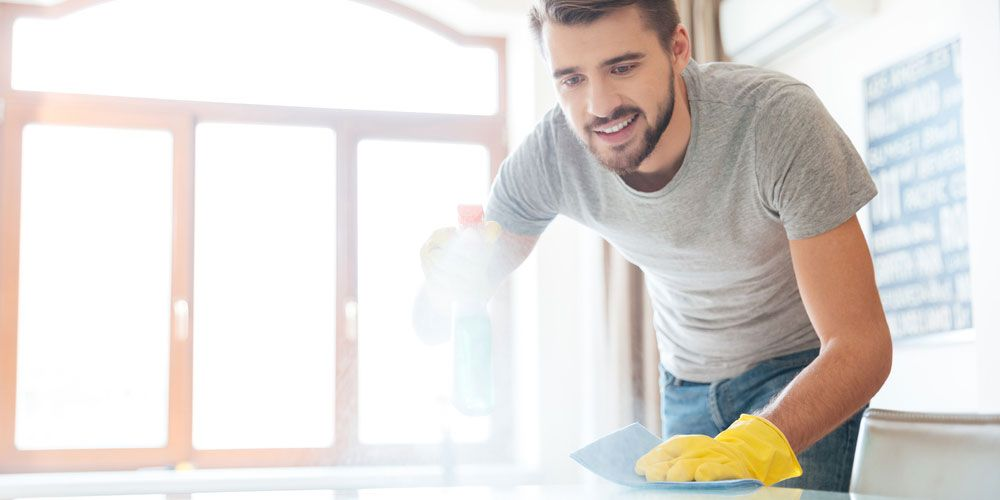 man cleaning floor with gloves.