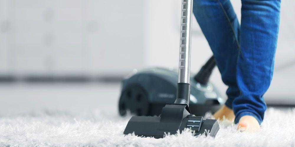 man vacuuming rug.