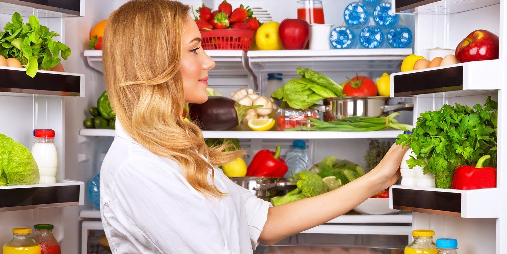 woman looking in filled refrigerator